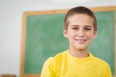 Lächelnder Schüler, der in einem Klassenzimmer sitzt stockbild