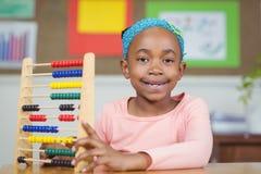 Lächelnder Schüler, der mit Abakus in einem Klassenzimmer berechnet Stockfoto