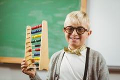 Lächelnder Schüler kleidete oben als Lehrer an, der Abakus hält Stockfotografie