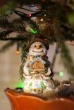 Lächelnder Schneemann des Spielzeugs Weihnachtsbaumspielzeug Drei Weihnachtskugeln getrennt auf Weiß Das Haus in den Händen Stockbild
