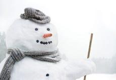 Lächelnder Schneemann draußen in den Schneefällen Stockfoto