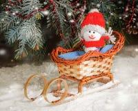 Lächelnder Schneemann Santa Toy, die in einem Pferdeschlitten im Winterwald sitzt Lizenzfreies Stockbild