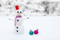 Lächelnder Schneemann und Weihnachtsdekorationen im Wald während Schneefälle Malerische Winterlandschaft Stockfotos