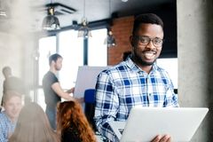 Lächelnder schwarzer Angestellter im überprüften Hemd, das an das Internet anschließt lizenzfreie stockfotos