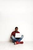 Lächelnder schwarzer Mann, der den Laptop sitzt auf dem Studioboden verwendet Stockfotografie