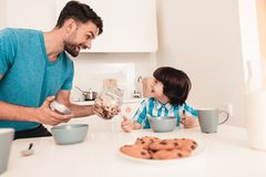 Lächelnder Sohn und Vater Have Breakfast in der Küche stockfoto
