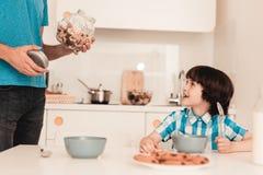 Lächelnder Sohn und Vater Have Breakfast in der Küche stockbild