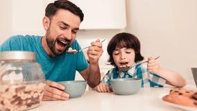 Lächelnder Sohn und Vater Have Breakfast in der Küche lizenzfreie stockfotos