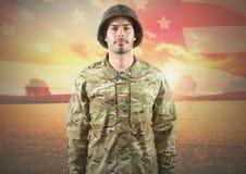 Lächelnder Soldat, der auf Hintergrund der amerikanischen Flagge steht Stockbild