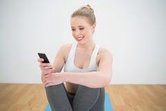 Lächelnder sportlicher blonder schauender Smartphone Lizenzfreies Stockfoto