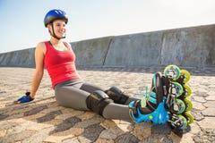 Lächelnder sportlicher blonder Schlittschuhläufer, der auf dem Boden sitzt Lizenzfreies Stockfoto