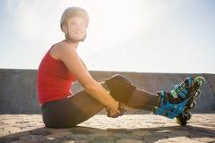 Lächelnder sportlicher blonder Schlittschuhläufer, der auf dem Boden sitzt Lizenzfreie Stockbilder