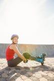 Lächelnder sportlicher blonder Schlittschuhläufer, der auf dem Boden sitzt Lizenzfreie Stockfotos