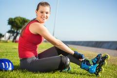 Lächelnder sportlicher blonder Schlittschuhläufer, der im Gras sitzt Stockfoto