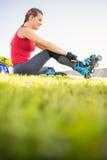 Lächelnder sportlicher blonder Schlittschuhläufer, der im Gras sitzt Stockbild