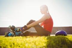 Lächelnder sportlicher blonder Schlittschuhläufer, der im Gras sitzt Lizenzfreies Stockfoto