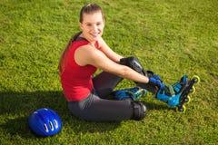 Lächelnder sportlicher blonder Schlittschuhläufer, der im Gras sitzt Stockfotografie