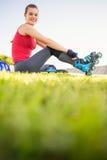Lächelnder sportlicher blonder Schlittschuhläufer, der im Gras sitzt Lizenzfreies Stockbild