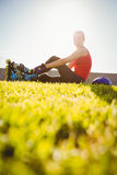 Lächelnder sportlicher blonder Schlittschuhläufer, der im Gras sitzt Lizenzfreie Stockfotografie