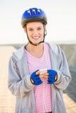 Lächelnder sportlicher blonder Schlittschuhläufer, der Musik genießt Stockfoto