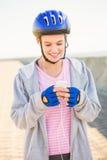 Lächelnder sportlicher blonder Schlittschuhläufer, der Musik genießt Stockbilder