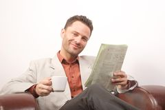 Lächelnder stattlicher Mann mit Zeitung und Tasse Kaffee - Portrait Stockfoto
