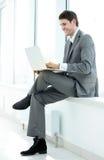 Lächelnder Student Blogger mit einem offenen Laptop, der nahe dem Gewinn sitzt Lizenzfreie Stockfotografie