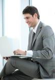 Lächelnder Student Blogger mit einem offenen Laptop, der nahe dem Gewinn sitzt Stockfoto