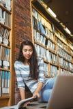 Lächelnder Student, der auf dem Boden gegen Wand in der Bibliothek studiert mit Laptop und Büchern sitzt Stockfotografie