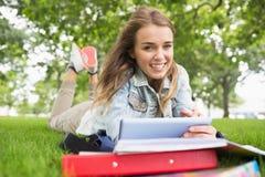 Lächelnder Student, der auf dem Gras studiert mit ihrem Tabletten-PC liegt Lizenzfreie Stockfotografie