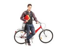Lächelnder Student, der Bücher nahe bei einem Fahrrad anhält Lizenzfreie Stockfotos