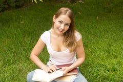 Lächelnder Student, der ein Buch liest stockfotografie