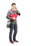 Lächelnder Student, der ein Inneres anhält und an einem Telefon spricht Lizenzfreies Stockfoto