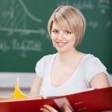 Lächelnder Student, der eine große Mappe hält Stockbilder