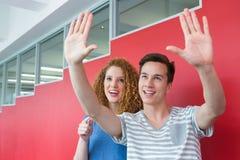 Lächelnder Student, der mit seinem Freund gestikuliert Stockfotografie