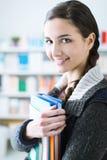 Lächelnder Student, der Notizbücher hält stockfoto