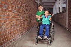 Lächelnder Student in einem Rollstuhl und in einem Freund neben ihm stockfoto