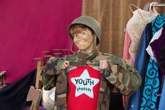 Lächelnder Student gekleidet als Armeemann Stockfotografie