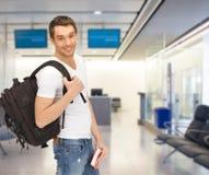 Lächelnder Student mit Rucksack und Buch am Flughafen stockfoto
