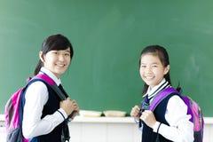 Lächelnder Student mit zwei Jugendlichen im Klassenzimmer stockfotografie
