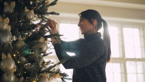 Lächelnder Student verziert die hängenden silbernen Bälle und Lichter des künstlichen Baums des neuen Jahres, welche die Niederla stock video