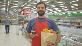 Lächelnder Supermarktangestellter, der Handy und das Halten der Einkaufstasche im Supermarkt verwendet stock video