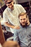Lächelnder talentierter Friseur, der bärtigen Kunden des Haarschnitts zu macht Lizenzfreies Stockbild