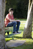Lächelnder Teenager, der auf Bank sitzt Lizenzfreie Stockfotos