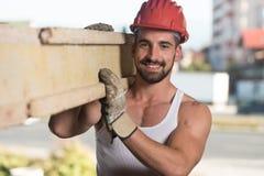 Lächelnder Tischler Carrying eine große hölzerne Planke auf seiner Schulter Stockfotografie