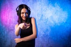 Lächelnder tragender Kopfhörer der Frau mit dem Mikrofon, das Finger auf Kamera Sie auf farbigem Neonhintergrund zeigend schaut stockfoto
