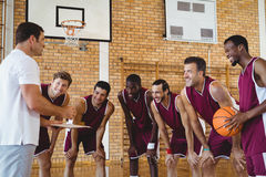 Lächelnder Trainer, der Strategie Basketball-Spielern erklärt Lizenzfreie Stockfotografie