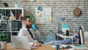 Lächelnder trinkender Kaffee des Büroangestellten und Entspannung während des Bruches bei der Arbeit stock video