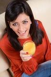 Lächelnder trinkender Orangensaft der Frau Stockbilder