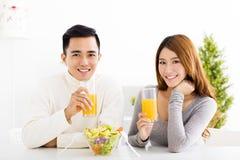 lächelnder trinkender Saft der Paare und gesundes Lebensmittel Stockfotos